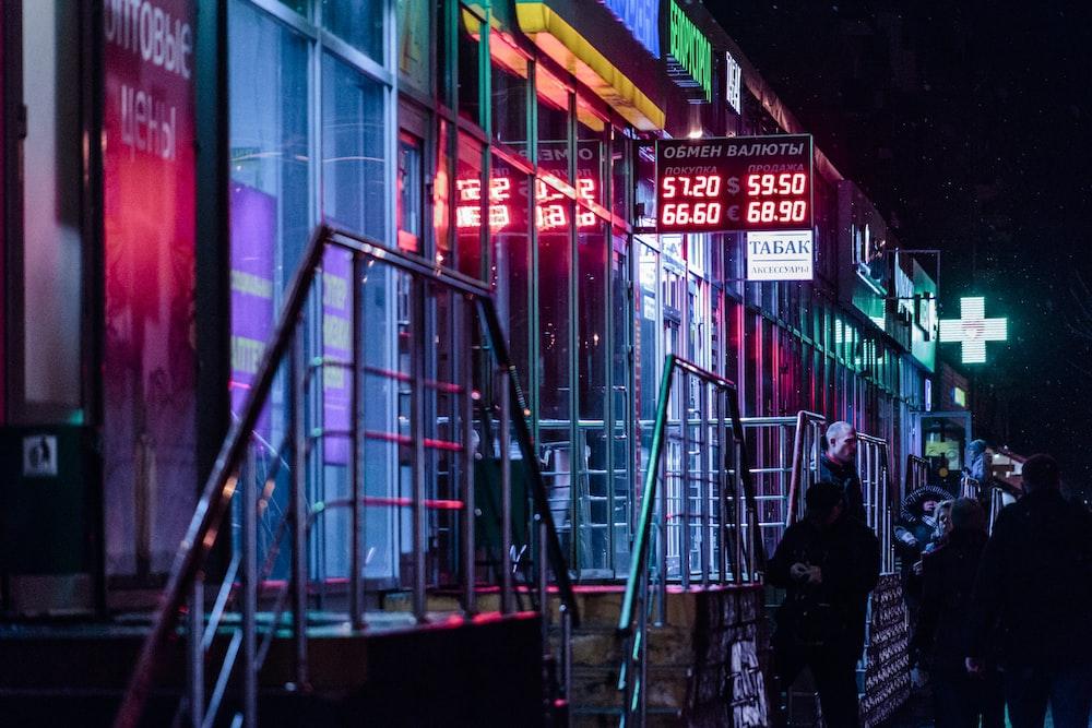夜の時間の間に赤と黄色の建物の近くに立っている黒いジャケットの男