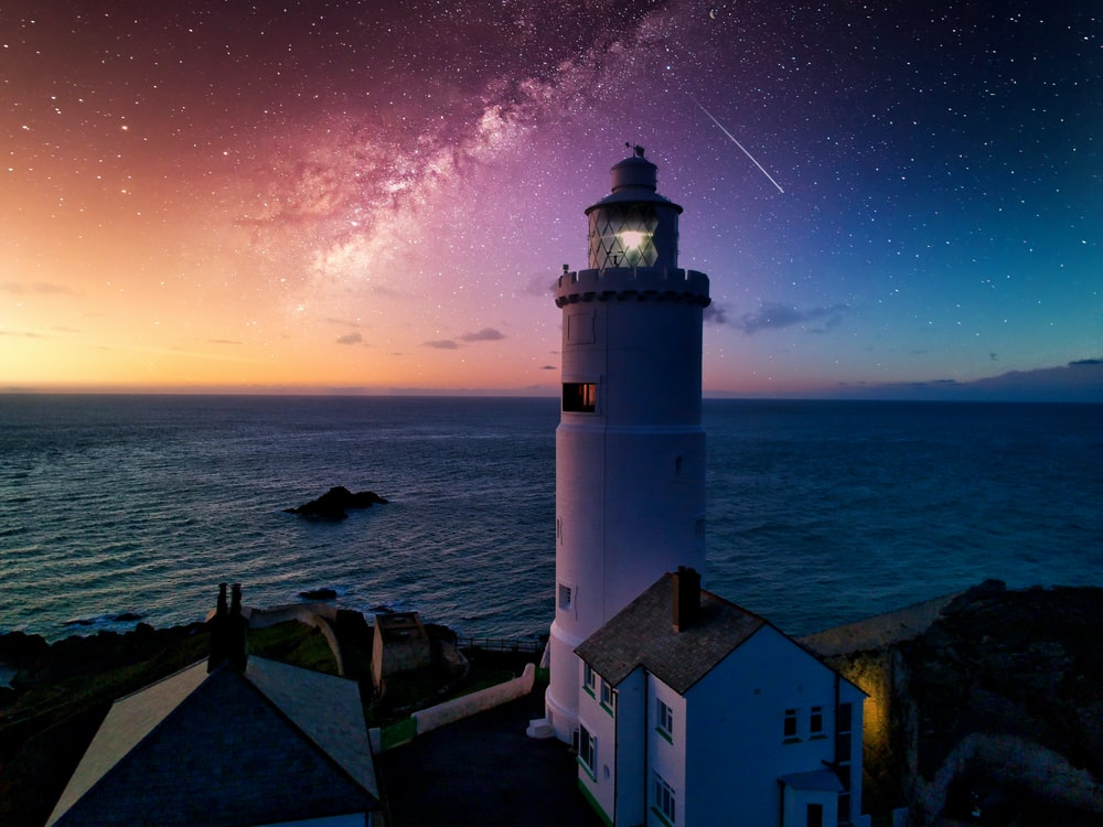 white and black lighthouse near body of water during night time