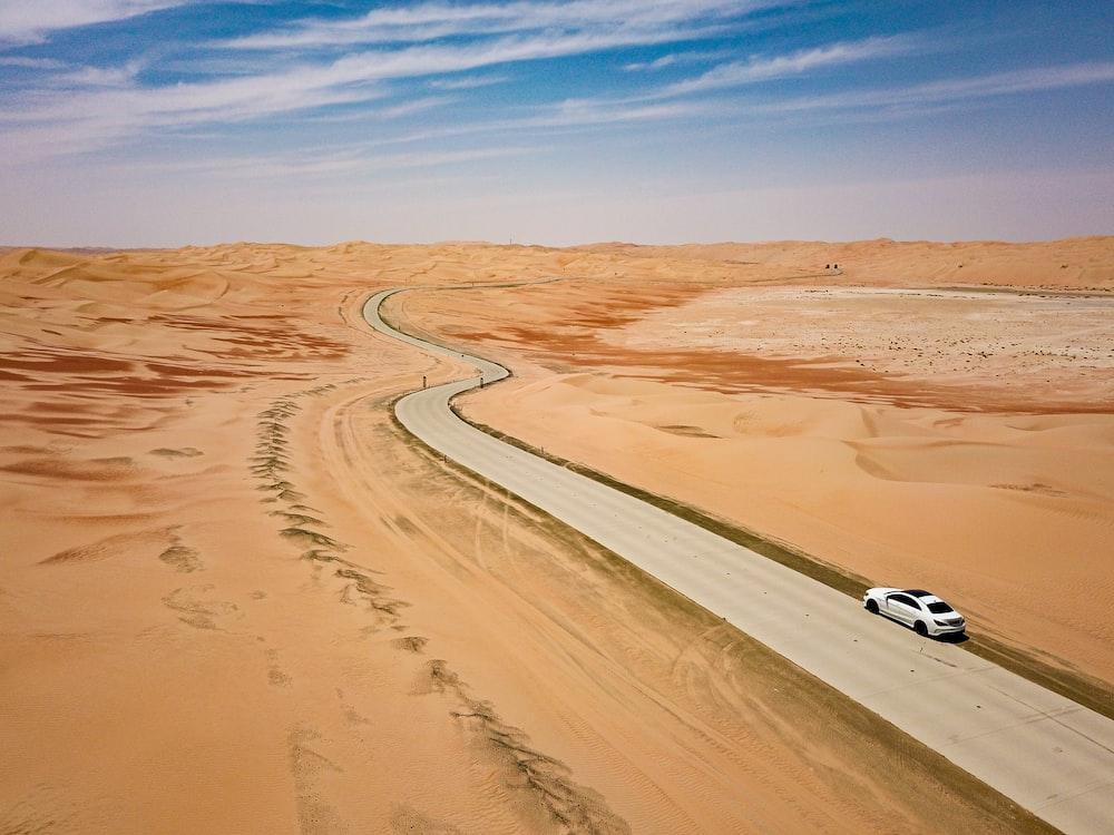 white car on brown sand