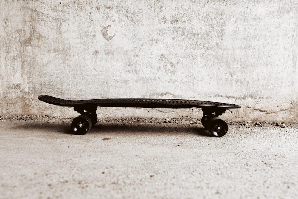 black skateboard leaning on white wall
