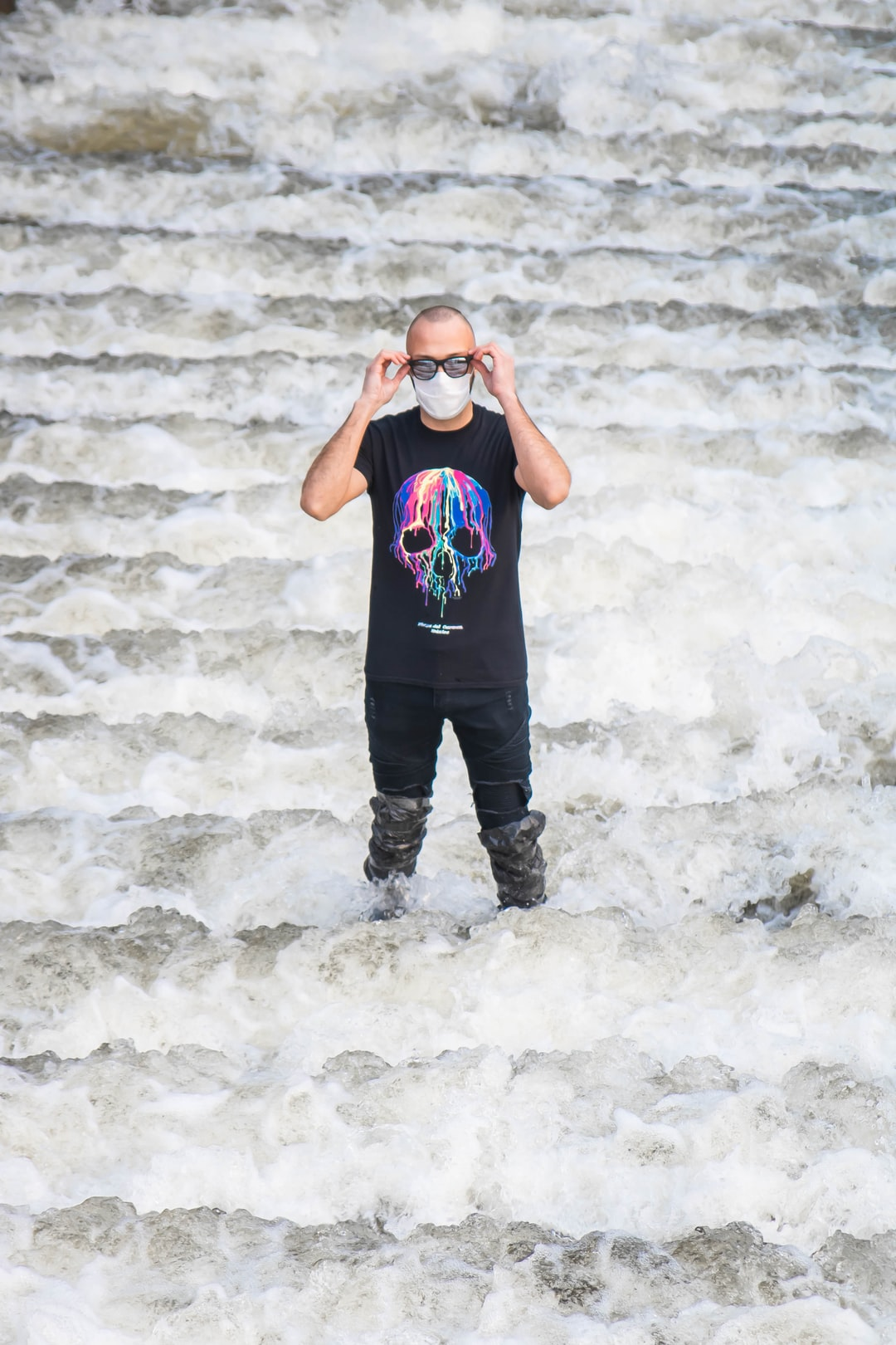 A man in glasses and a mask stands in the water
