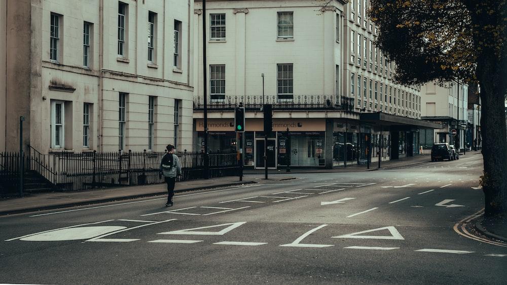 man in black jacket walking on pedestrian lane during daytime