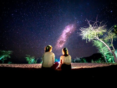 man and woman sitting on ground under starry night malawi zoom background