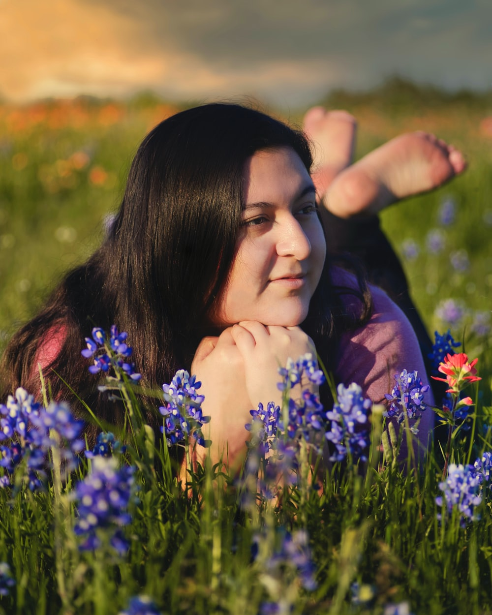 woman in purple shirt lying on green grass field during daytime