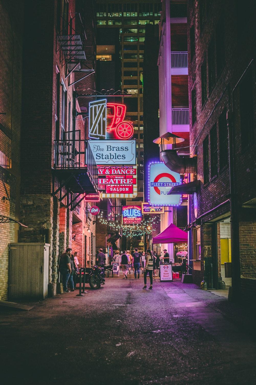 people walking on sidewalk near store during night time