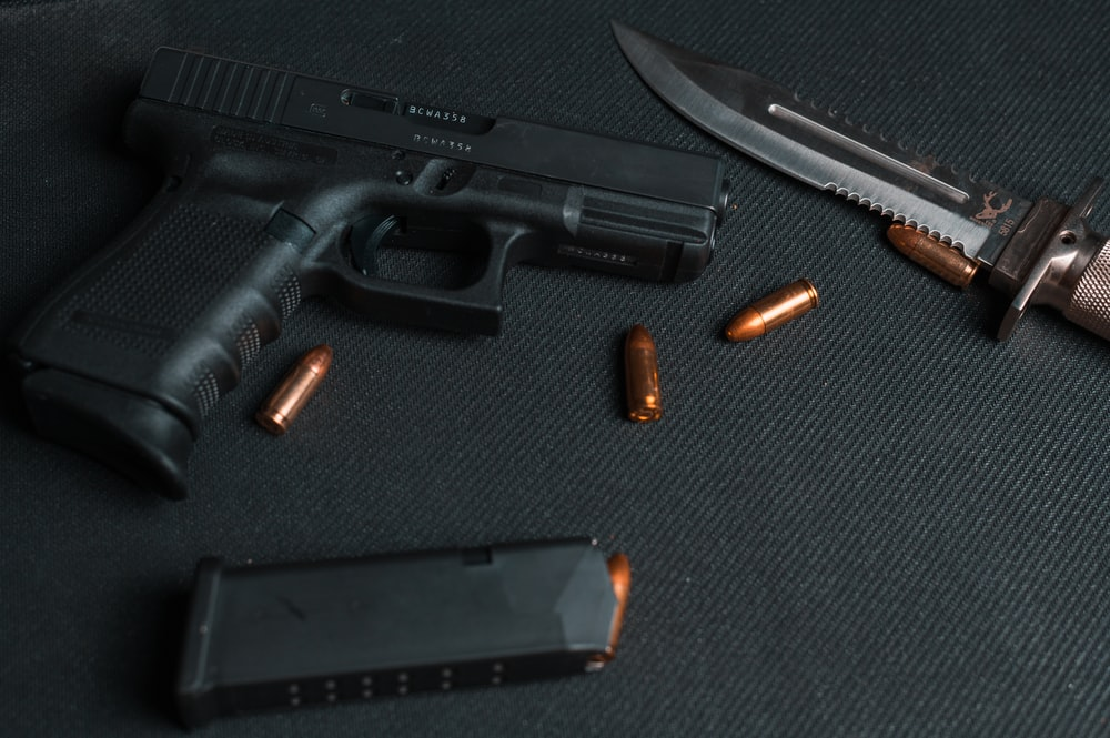 black semi automatic pistol beside brown and silver pocket knife