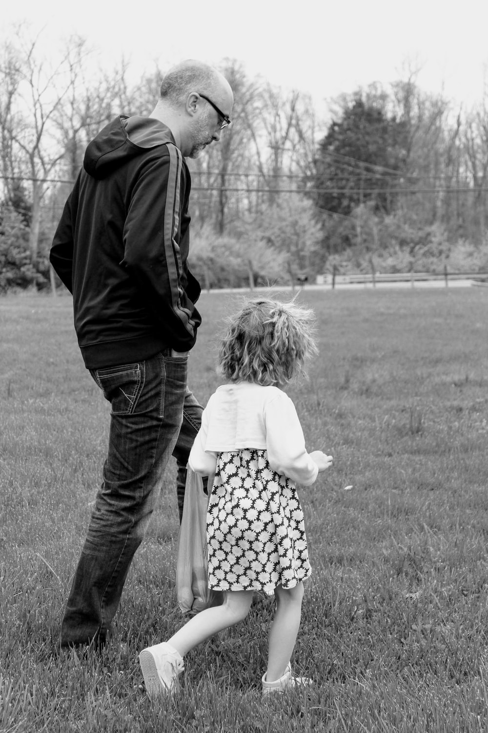 grayscale photo of man and woman walking on grass field