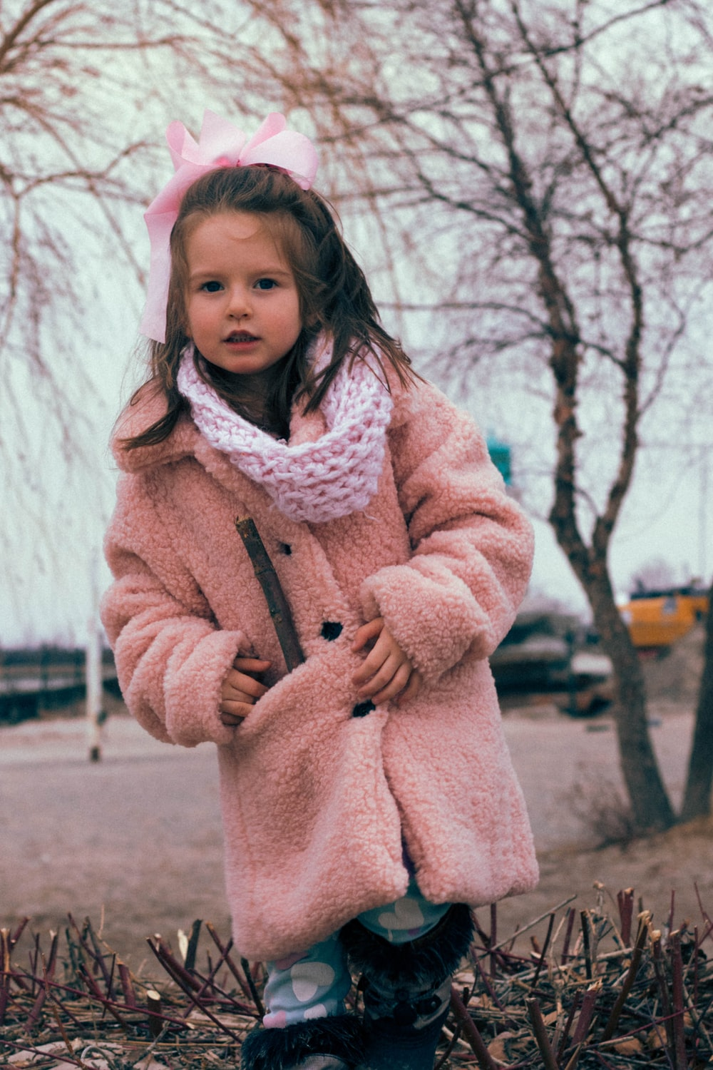 girl in pink coat standing on brown field during daytime