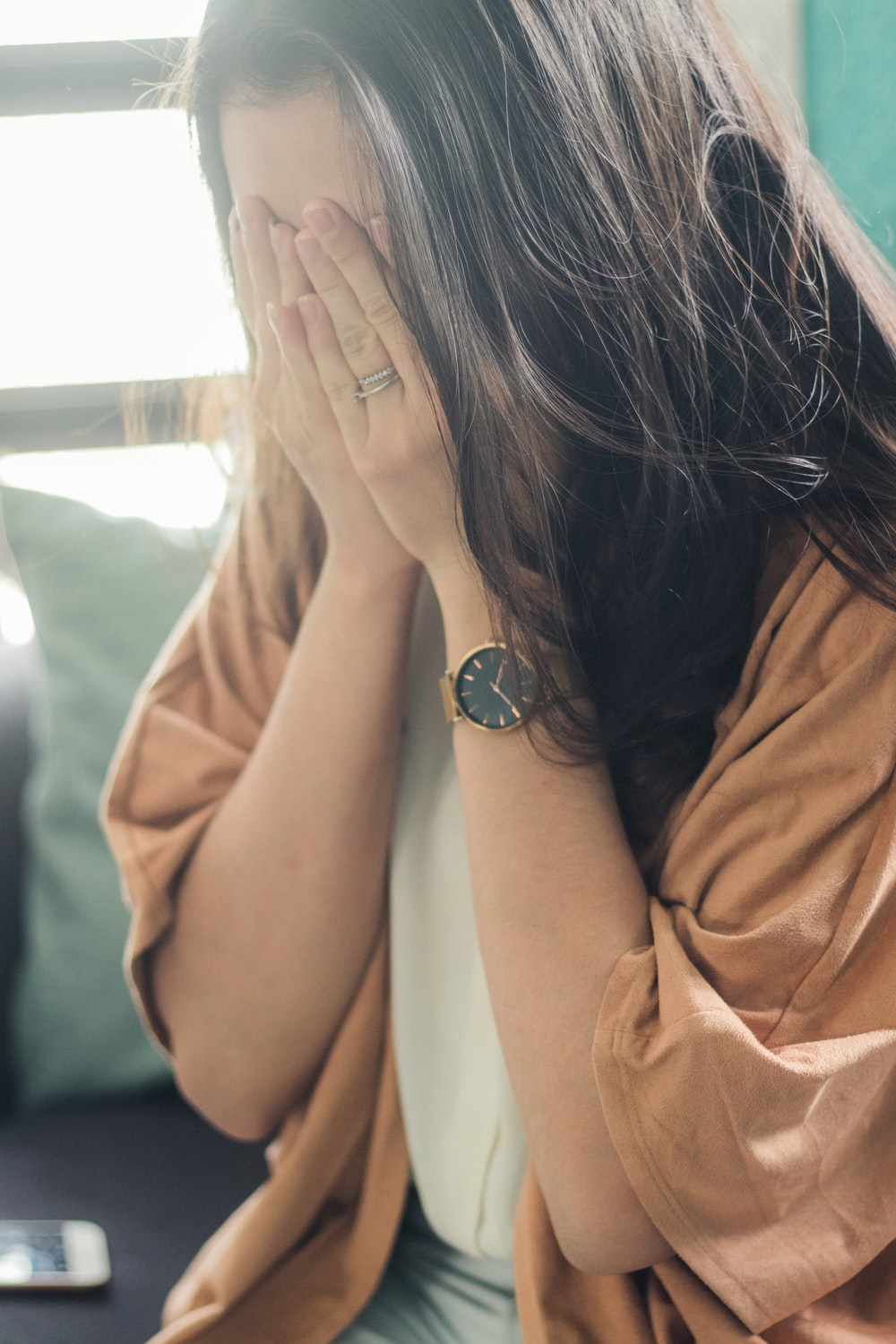 woman in brown shirt covering her face