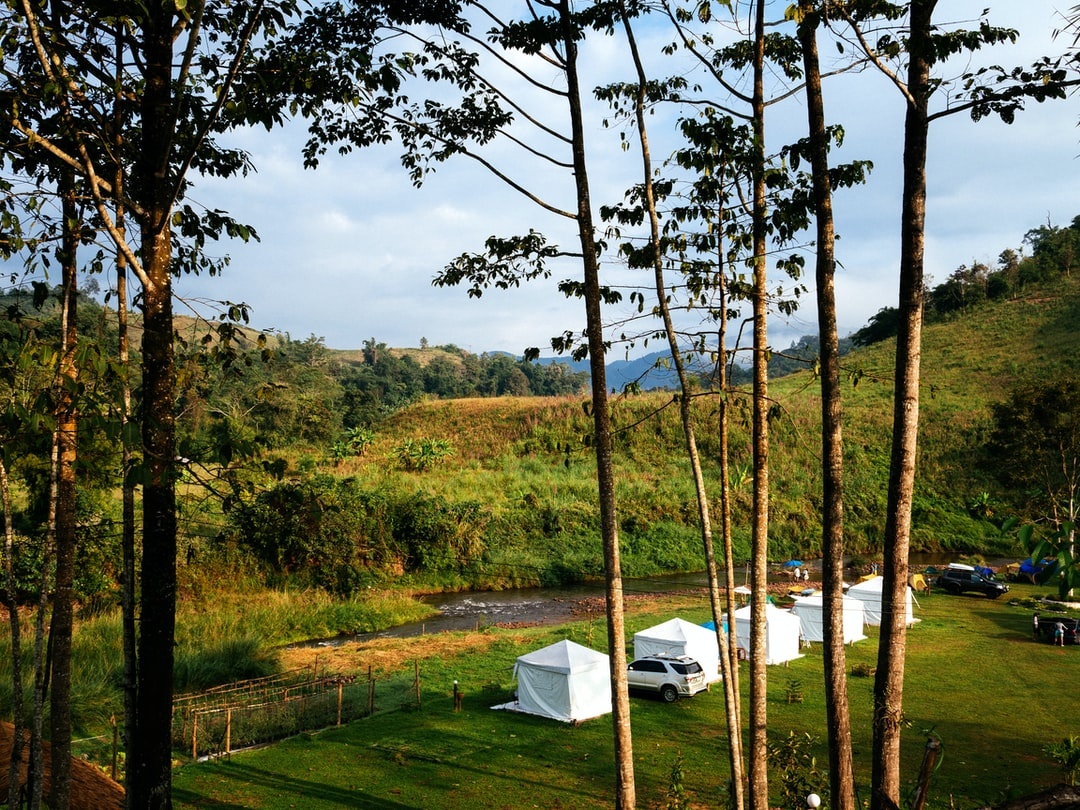 white camping tents beside a river