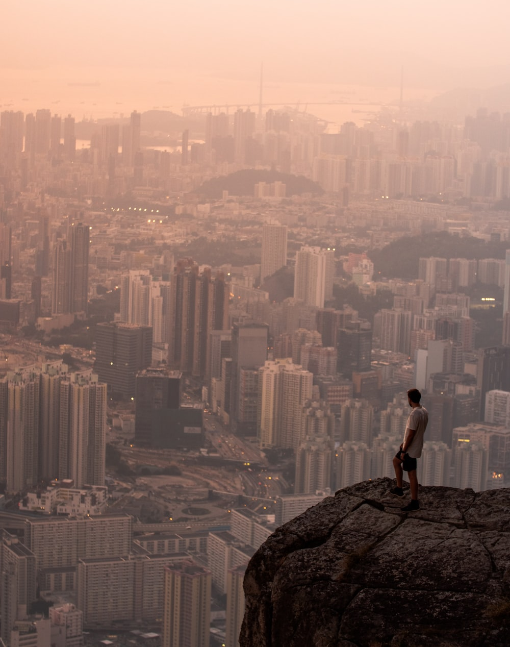man sitting on rock looking at city skyline during daytime