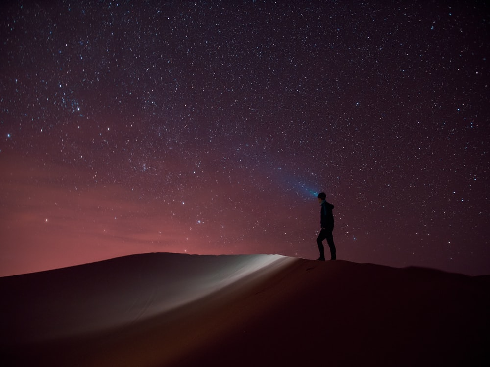 silhouette of person standing on sand during night time