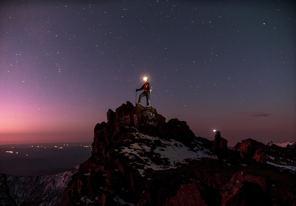 person standing on rocky hill during night time