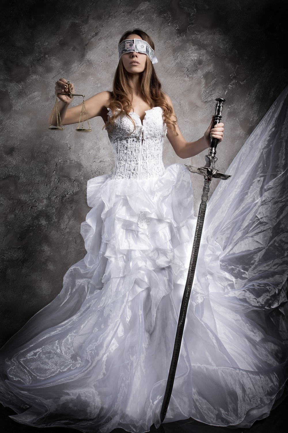 woman in white dress holding black and silver sword