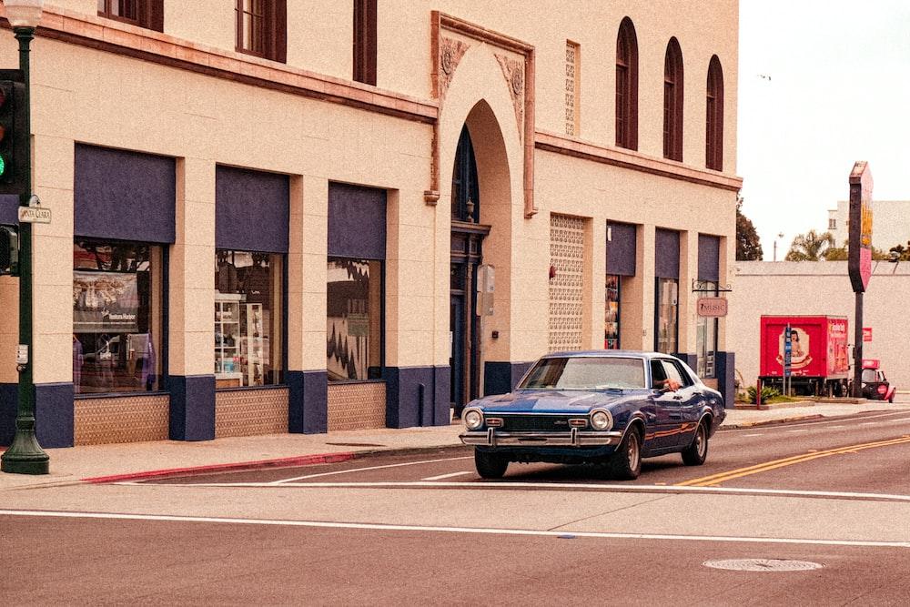 black sedan parked beside brown concrete building during daytime