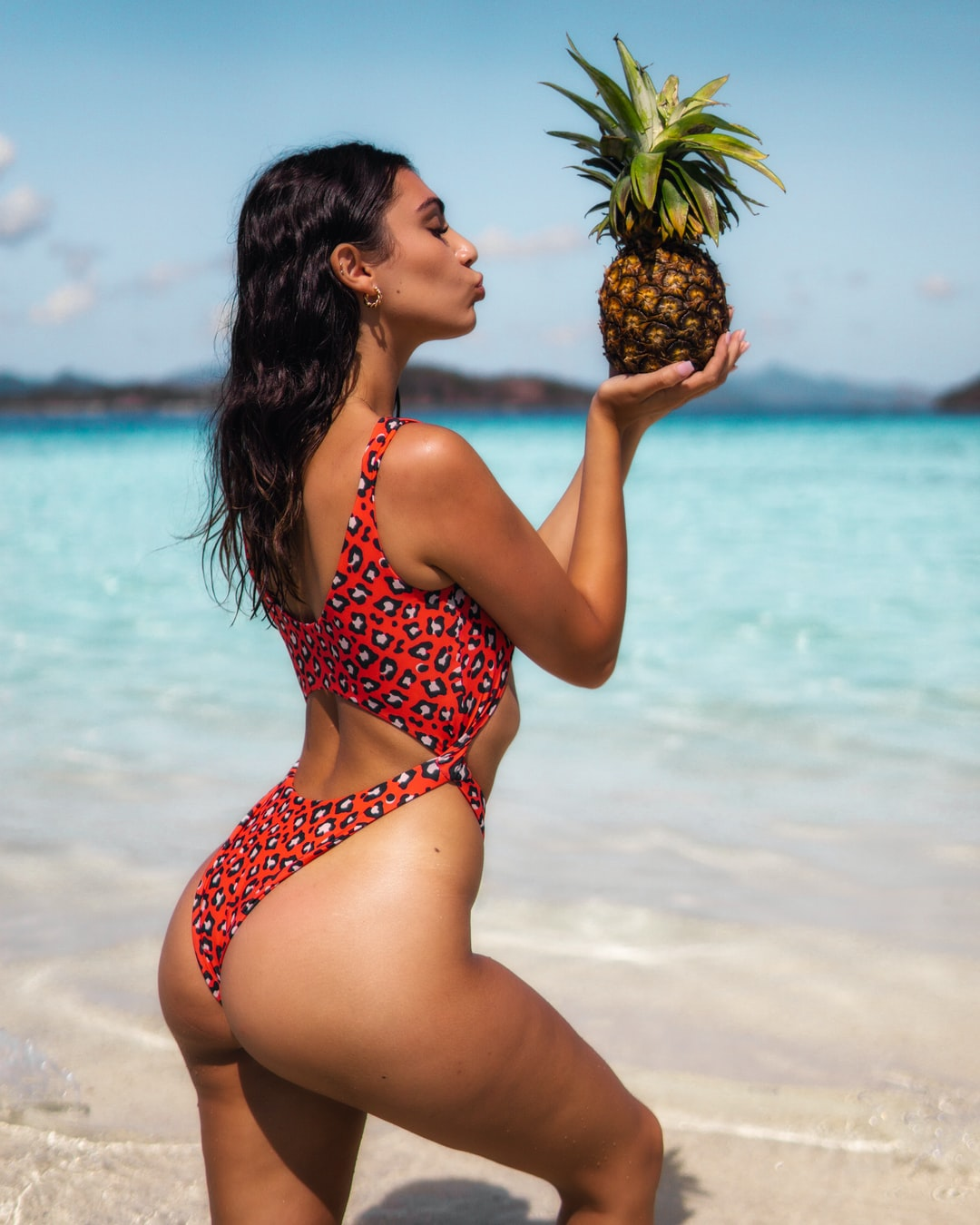 Beautiful girl in The Wild Swim swimsuit bikini kissing a pineapple on the tropical island on a beach in the Philippines