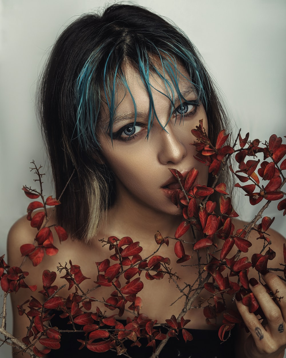 woman with blue hair and red flowers