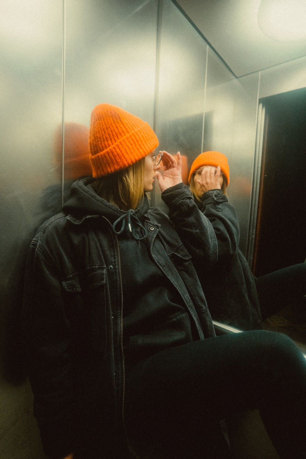 woman in black leather jacket and orange knit cap