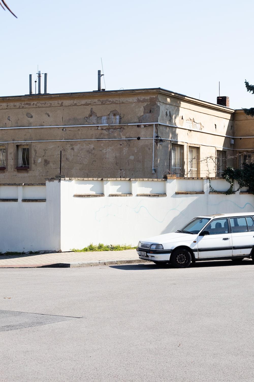white sedan parked beside white concrete building during daytime