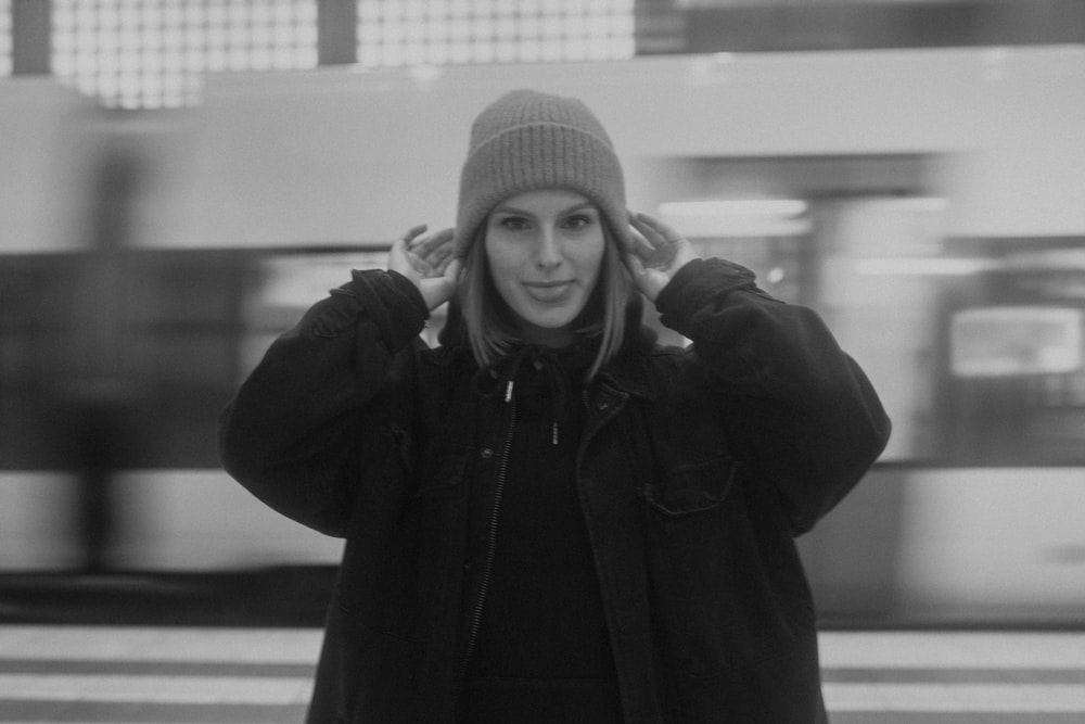 grayscale photo of woman in knit cap and jacket