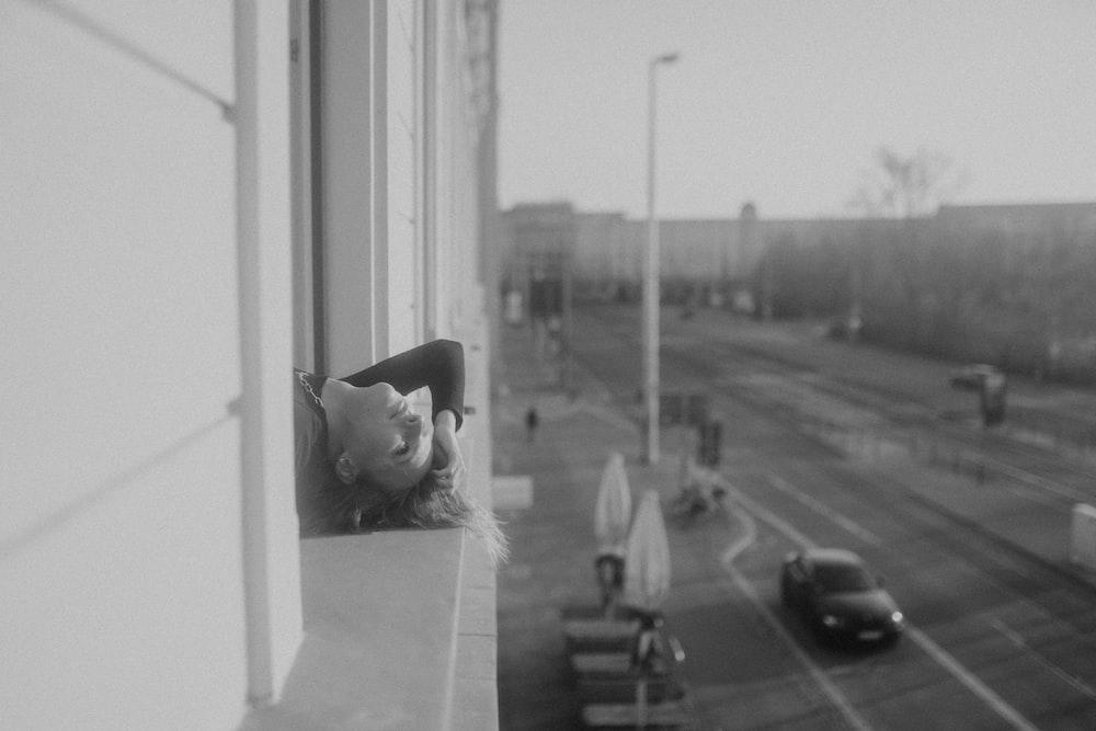 grayscale photo of cat on window