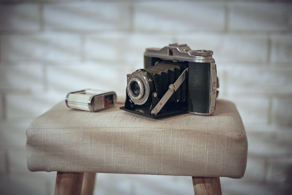 black and silver camera on brown wooden table