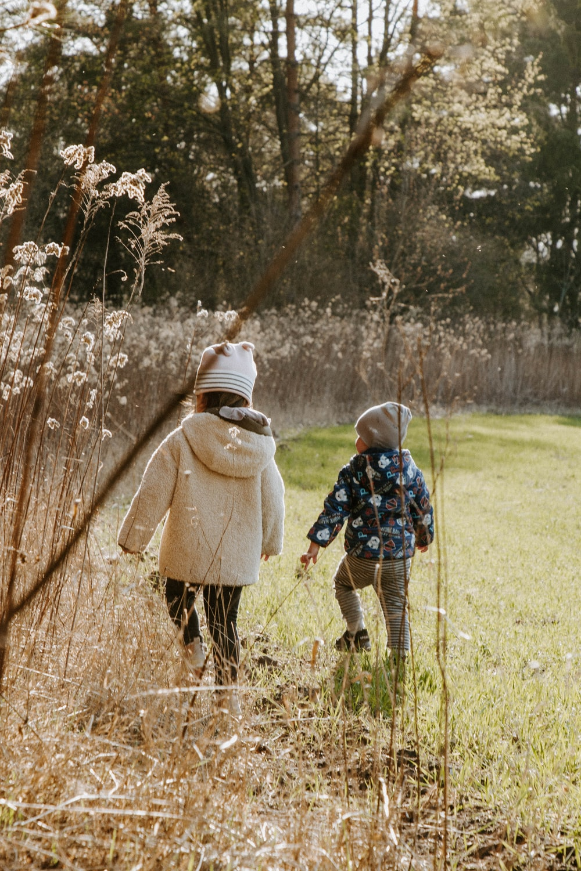 2 children standing on green grass field during daytime