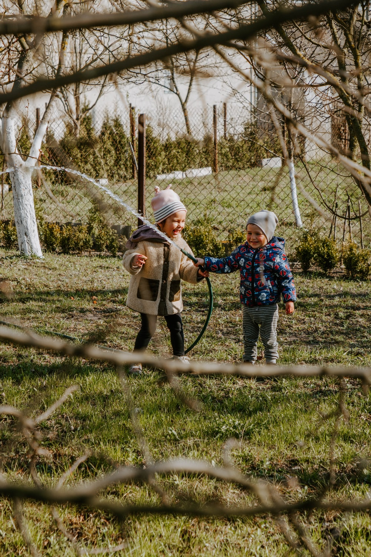 2 children holding brown wooden stick standing on green grass field during daytime
