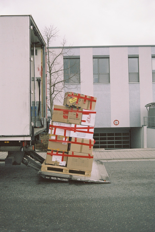 brown cardboard boxes on gray asphalt road