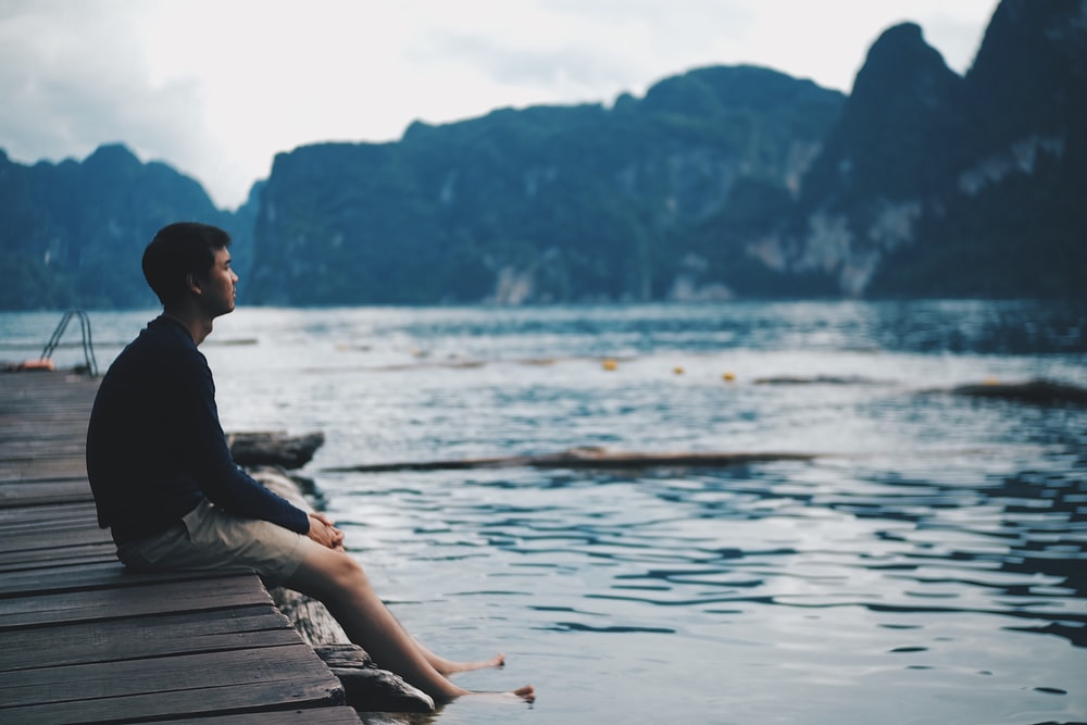 man in black jacket sitting on wooden dock during daytime