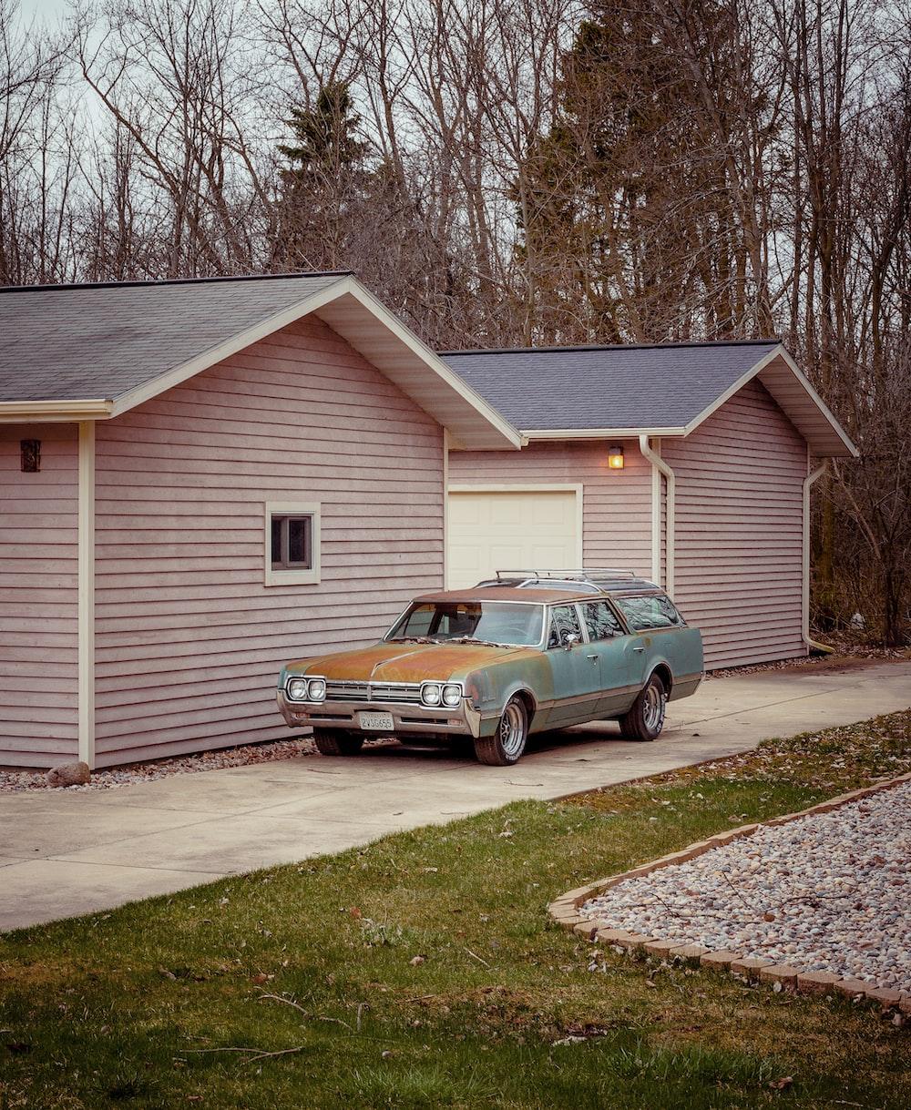 black sedan parked beside white wooden house