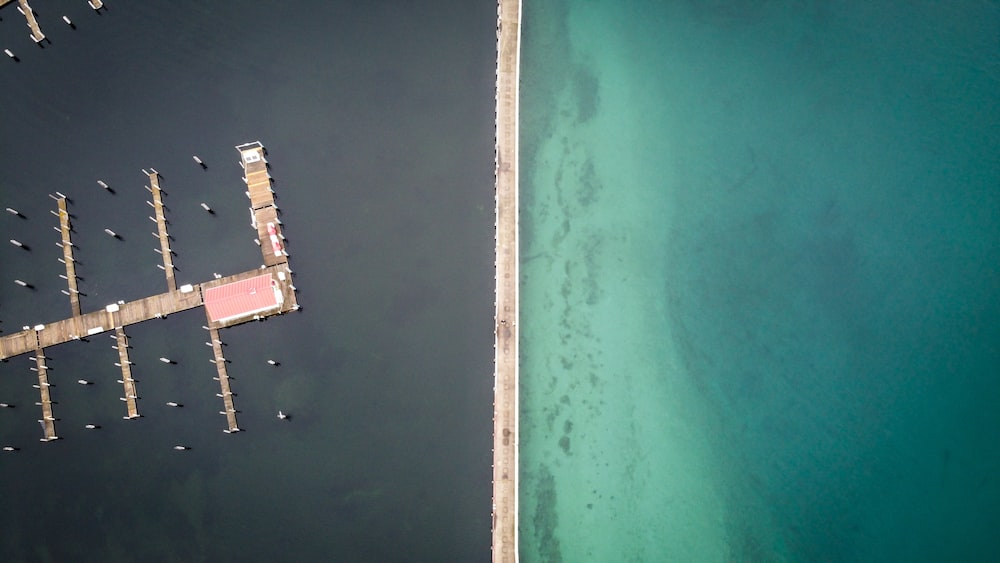aerial view of white and brown dock on body of water during daytime