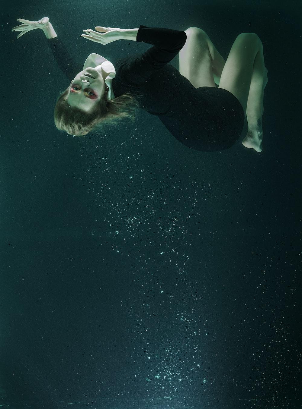 woman in black tank top and black pants under water