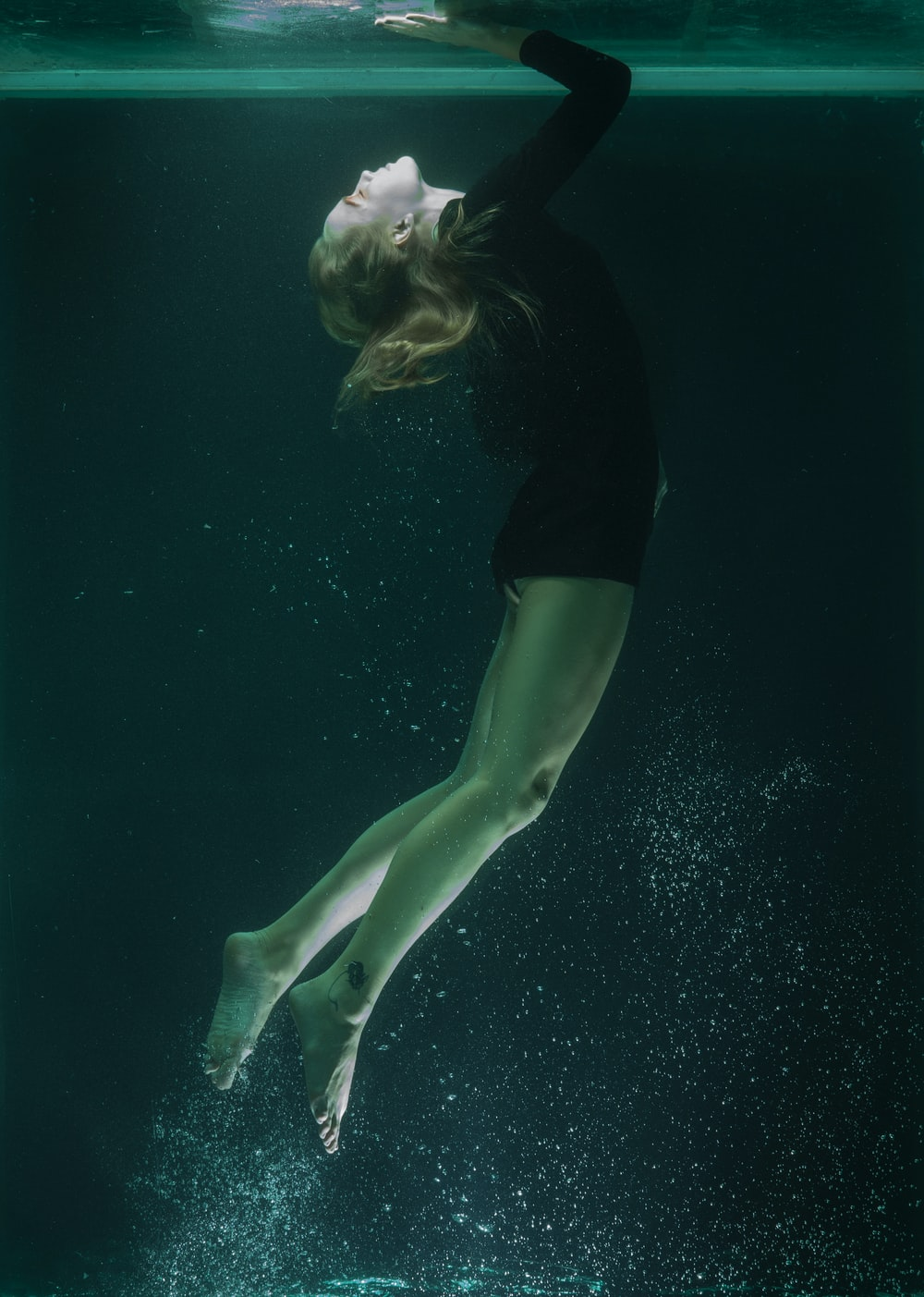 woman in black shirt and green shorts in water