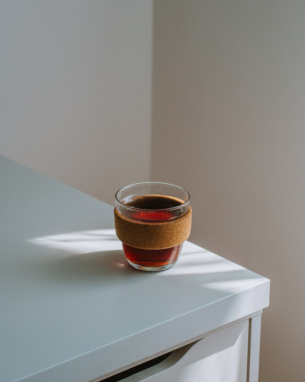 brown glass cup on white table