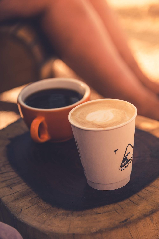 white and orange ceramic mug with coffee