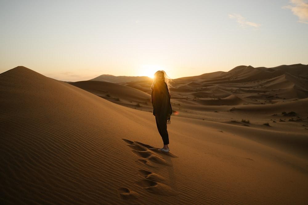 woman in brown jacket walking on desert during daytime