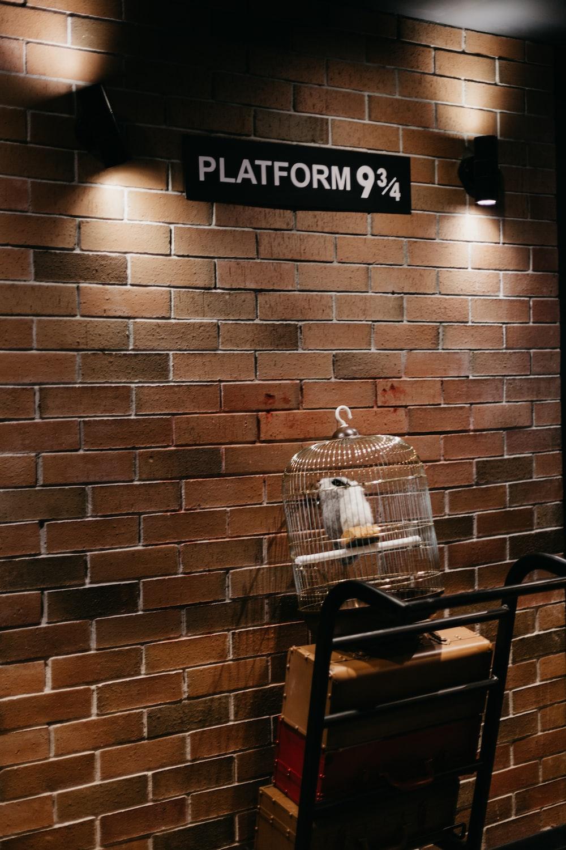 black metal armchair beside brown brick wall