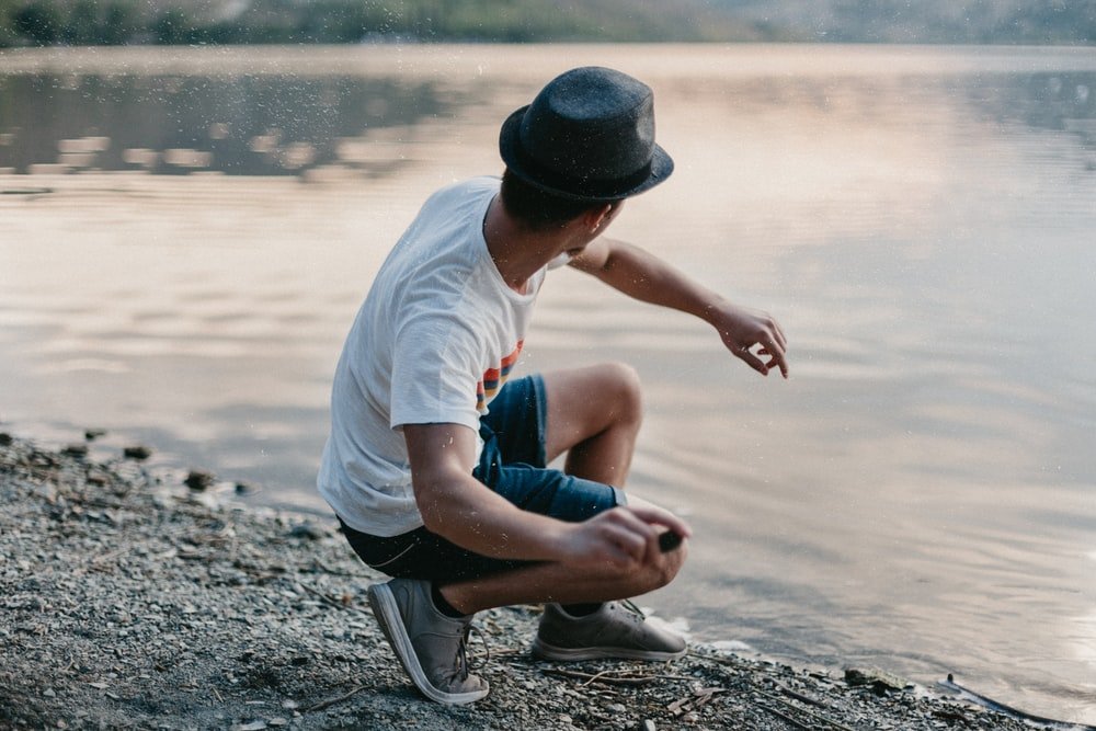 man in white t-shirt and blue denim shorts sitting on rock near body of water