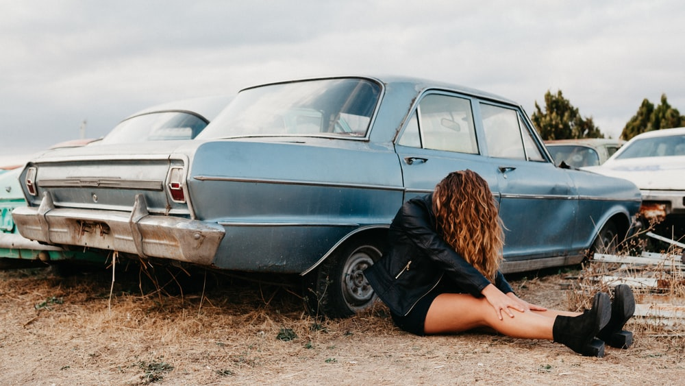 woman in black jacket leaning on teal car