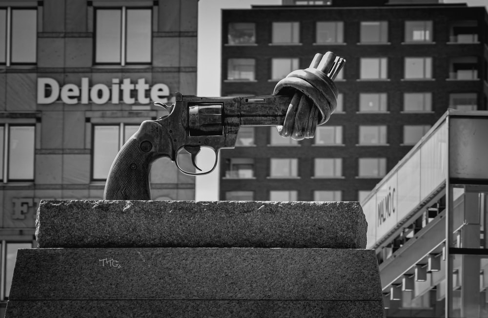 grayscale photo of a black and white photo of a person holding a airsoft pistol