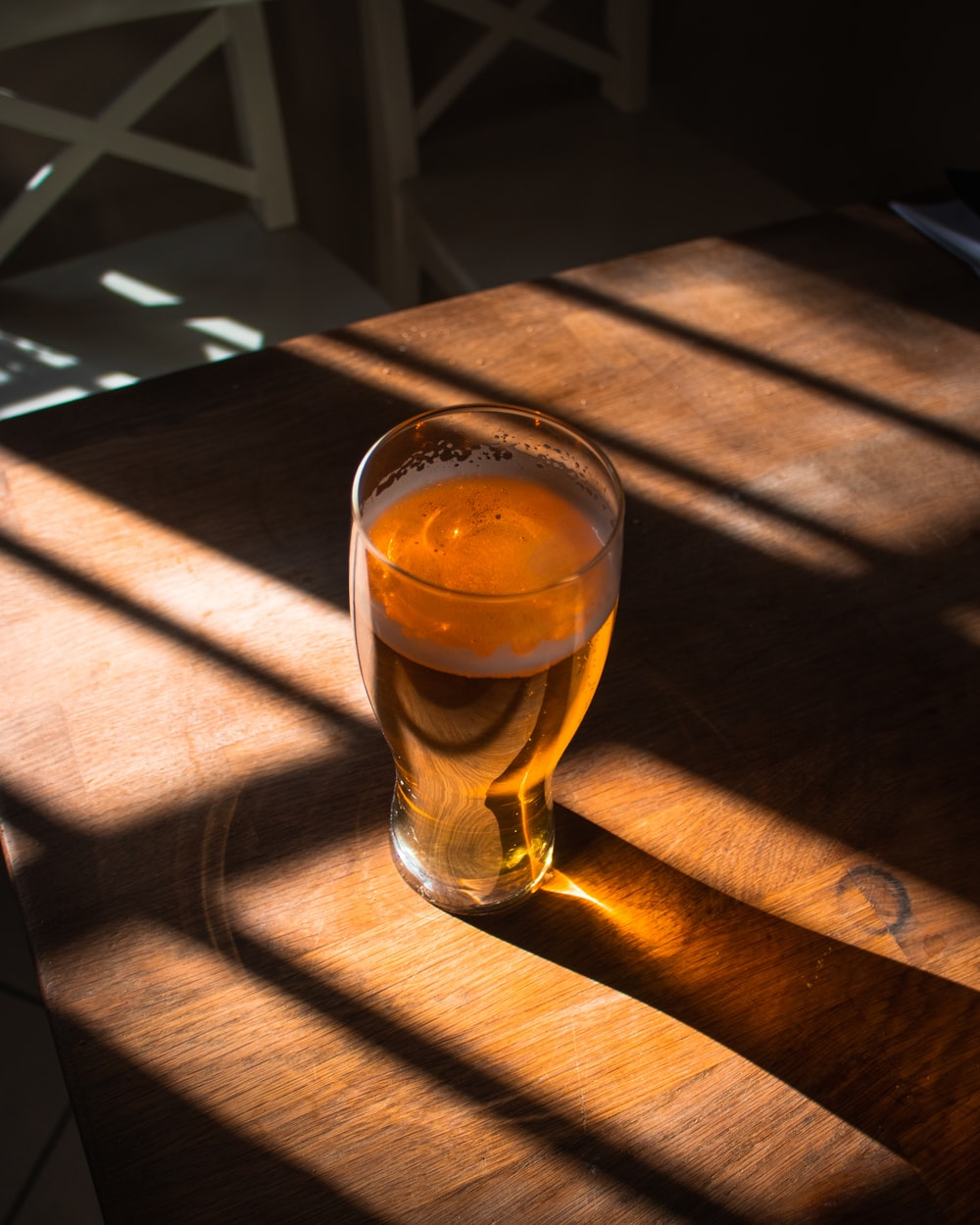 clear drinking glass with brown liquid on brown wooden table
