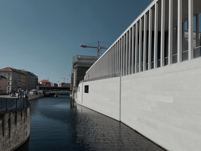 white and black concrete building near body of water during daytime