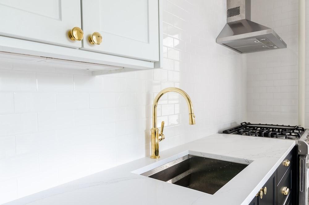 white wooden door beside stainless steel sink