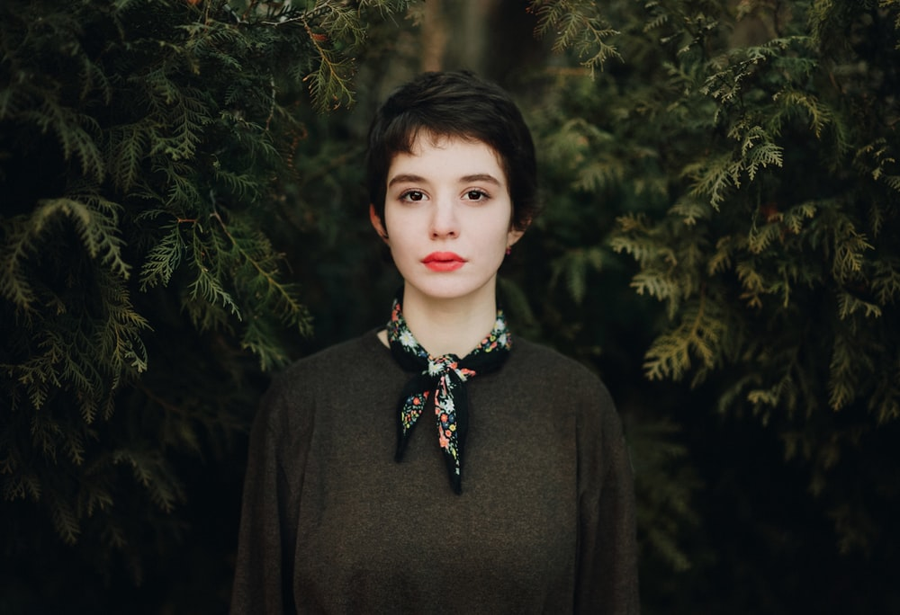 woman in black turtleneck sweater standing near green trees during daytime