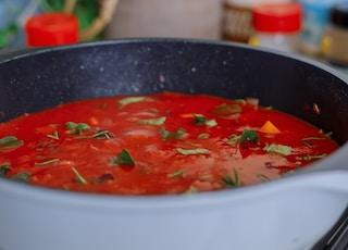red soup in black ceramic bowl