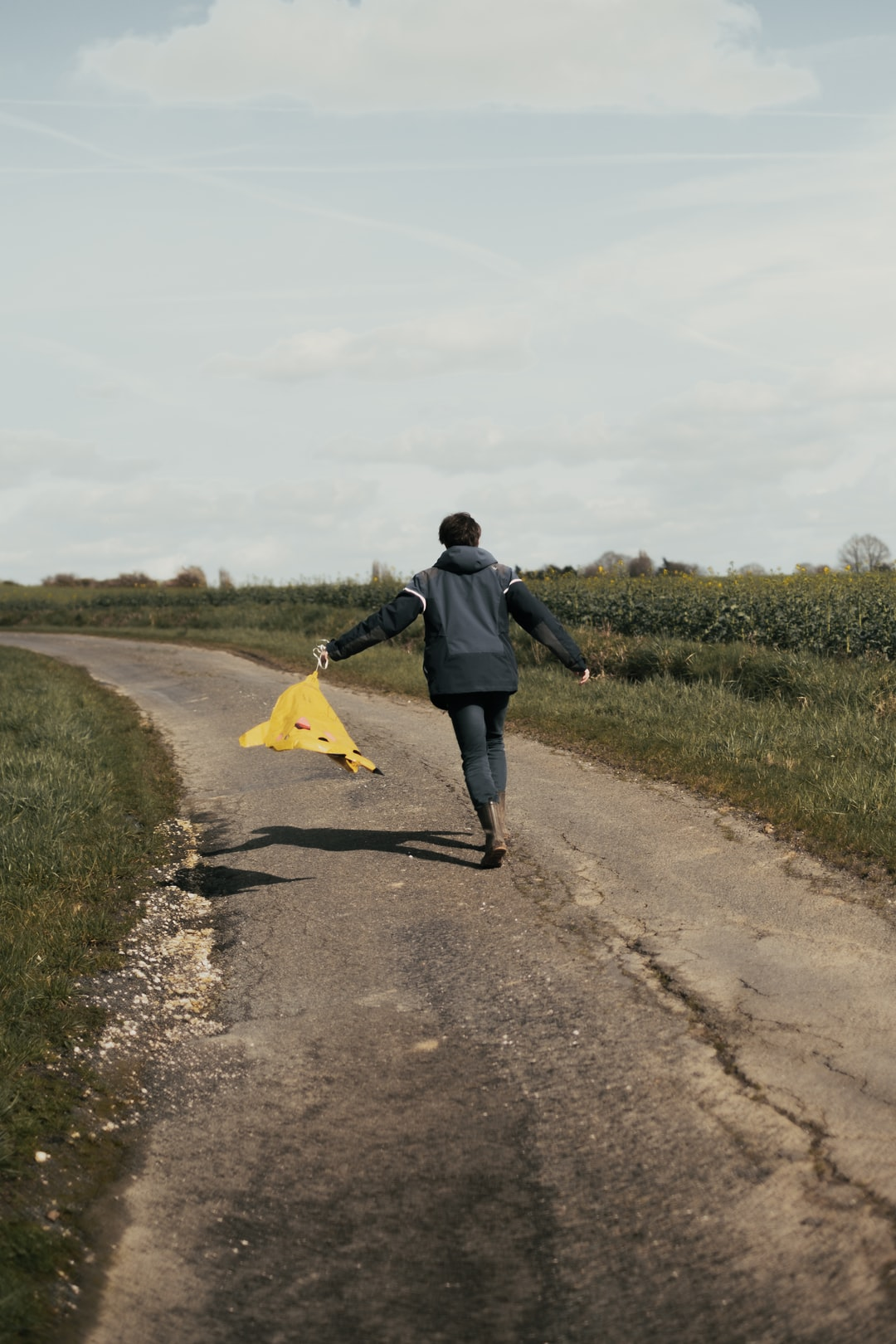 Young man running in the country side, holding a Pikachu balloon