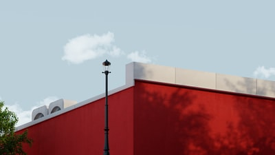 red and white concrete building under white sky during daytime post-impressionism zoom background