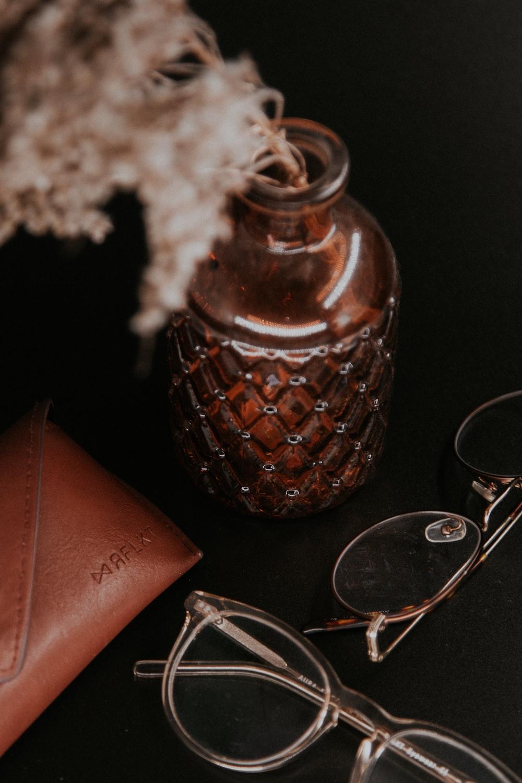 brown ceramic jar beside silver framed eyeglasses