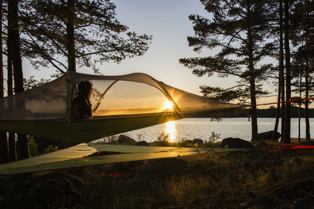 brown tent near body of water during sunset